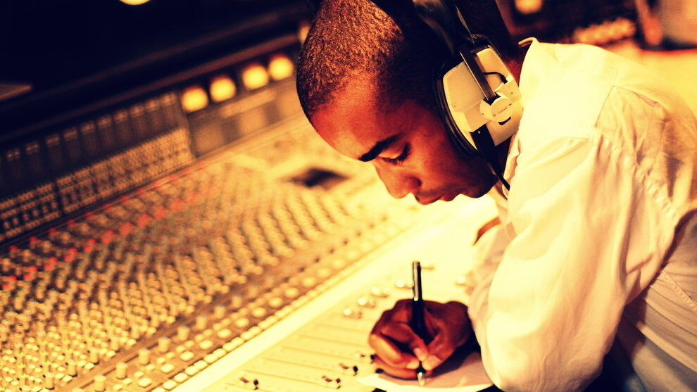 Peter sat at a sound-desk, headphones on