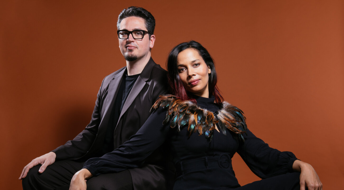 Multiethnic lady in black clothes and feather shrug sits and leans on Italian man in dark suit and black glasses sitting behind