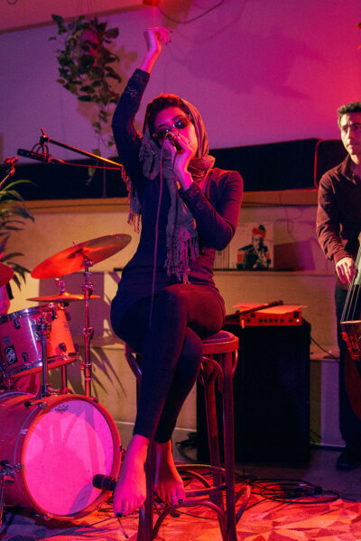 Judi Jackson wearing sunglasses singing whilst sitting on a chair with drummer and bassist in background, lit by pink light