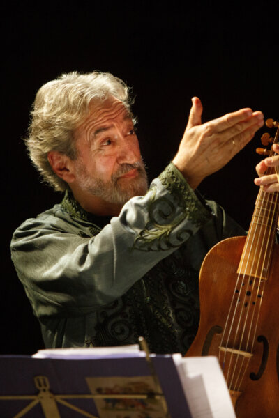Catalan man holding viol and raising his hand and smiling music stand