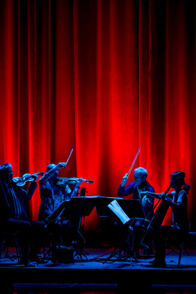 Blue lit string quartet playing wildly against a bright red curtain