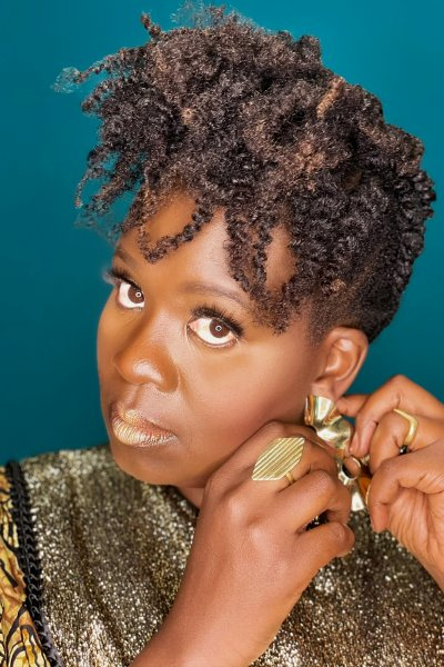 Black woman wearing gold patterns adjusts gold earring in front of teal background