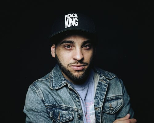 Bearded man in denim jacket wearing black cap with PEACE KING sewn in white