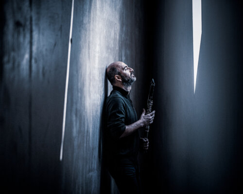 Syrian man in black clothing leans against grey wall holding clarinet with light rays cutting past