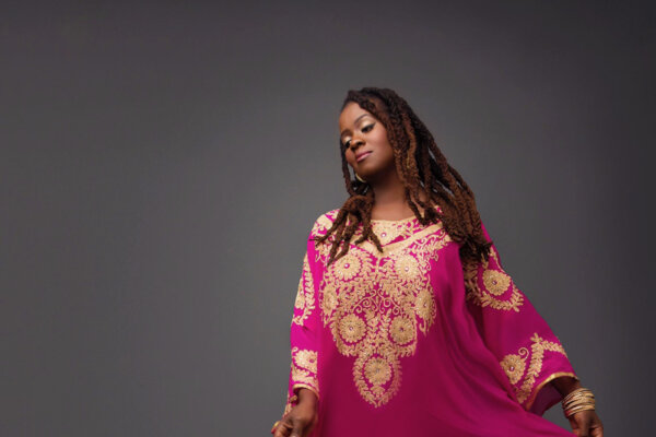 Black lady barefoot dancing in a flowing bright pink and elaborately gold decorated dress against a grey background