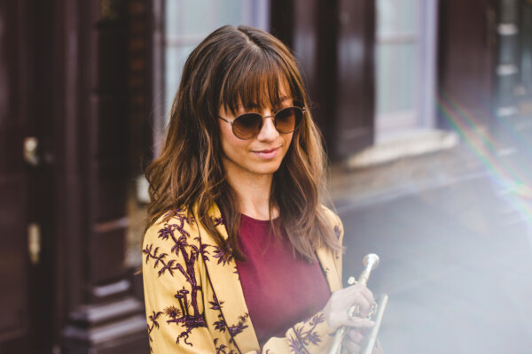 Yazz Ahmed, in a street, holding saxophone, wearing sunglasses