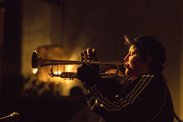 Profile of musician playing trumpet with yellow backlight