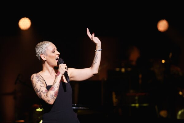 Tattooed performer singing and waving